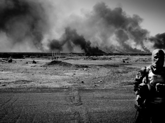 Iraqi Special Forces soldier during advance on Mosul with oil installations blown up by Daesh burning near Qayyarah. Standing in the foreground with billowing smoke in the distance over the desert.