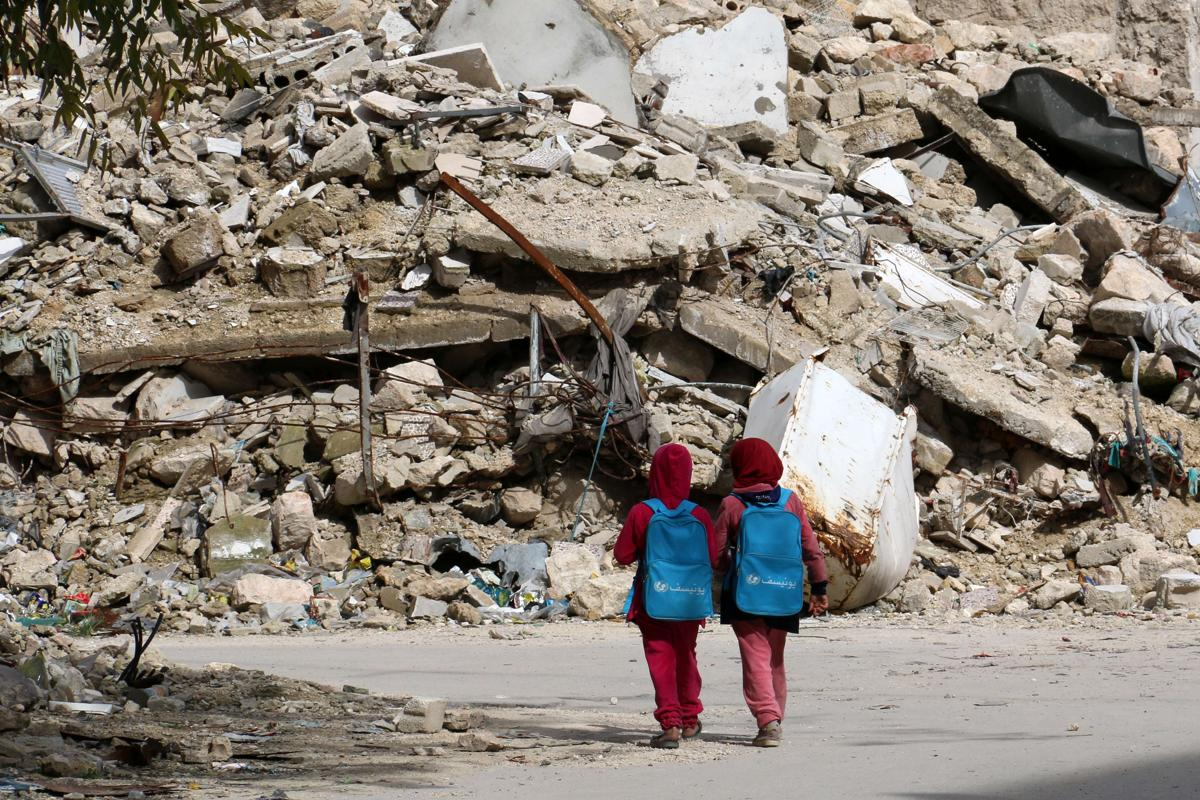 Syrian girls, carrying school bags provided by UNICEF, walk past the rubble of destroyed buildings on their way home from school on March 7 in al-Shaar neighborhood, in the rebel-held side of the northern Syrian city of Aleppo. (IZEIN ALRIFAI/AFP/GImages)