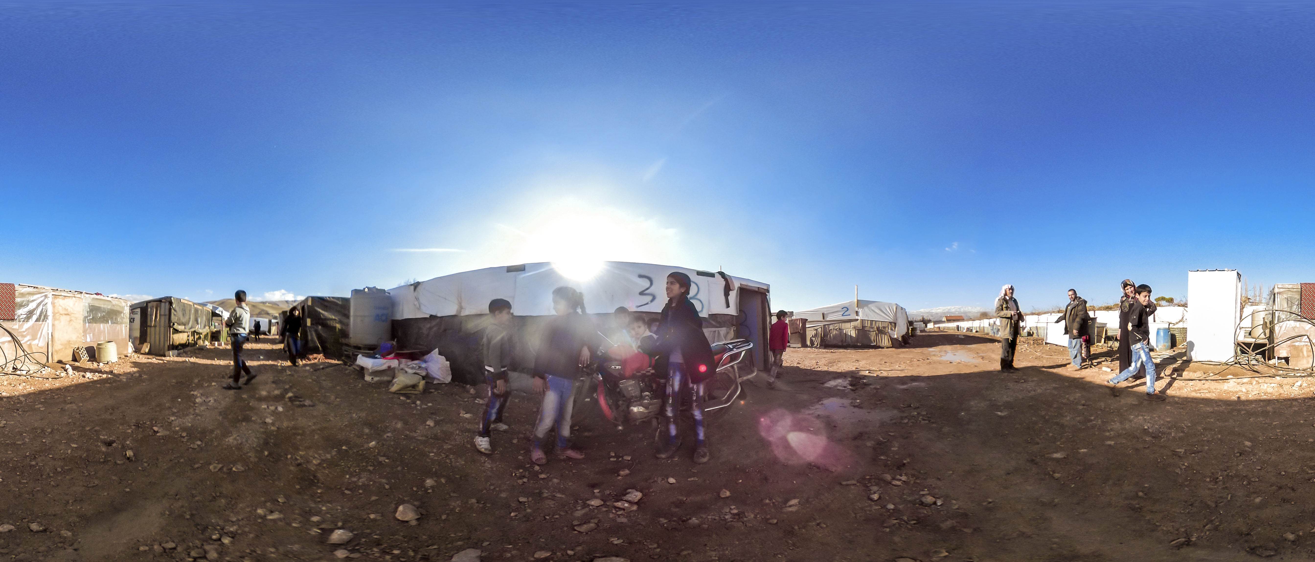 A group of children play in front of a motorbike in a tented refugee camp in the Bekaa Valley, Lebanon. Several older people look on from the right. Tents and shacks are behind the motorbike. The sun shines brightly. The image has a fish-eye effect.