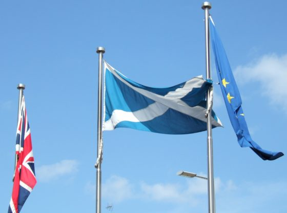 Flags outside the Scottish Parliament in Edinburgh, Scotland. Left to right: British flag, Scottish flag, European Union flag. The Scottish flag is unfurled. The others hang limply by their flagpoles.