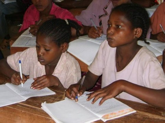 Two Ethiopian girls in class in a school supported by LCDI, Wolaita Zone, Ethiopia, 2015. Both are writing in jotters. One pays close attention to what the teacher is saying.