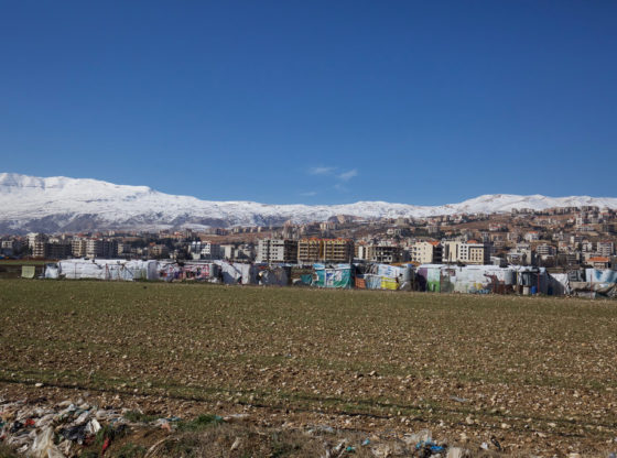 An informal tented settlement of Syrian refugees in the Bekaa Valley, Lebanon. A series of temporary shacks are in the foreground next to a ploughed, rocky field. The apartment blocks of a town are in the background. Snow covered hills are on the horizon.