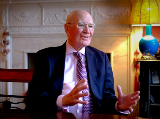 Menzies Campbell at home in Edinburgh. He faces the camera smiling. He is wearing a blue suit, shirt and tie. His arms bent and apart.
