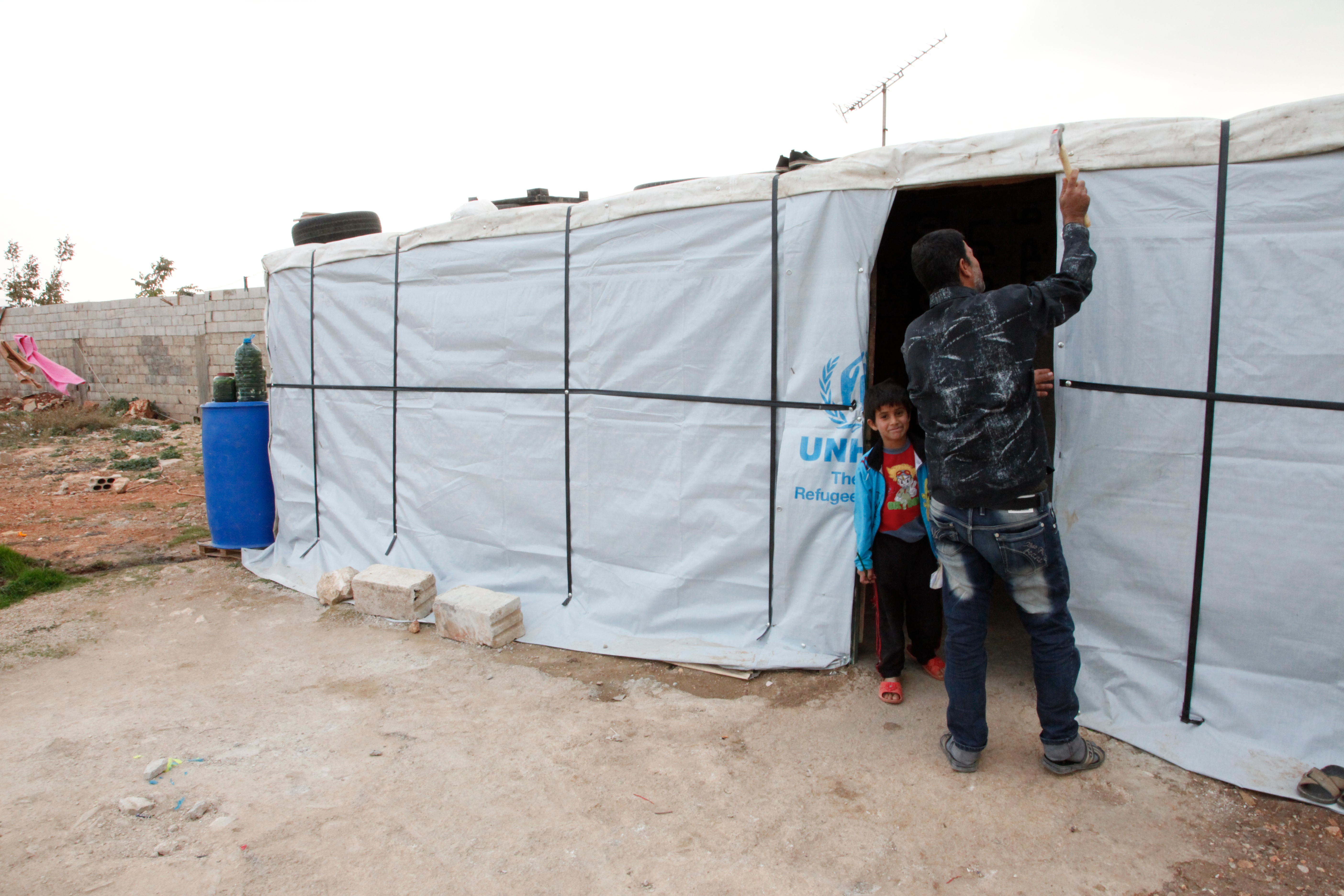 A man ties up the cloth entrance to his UNHCR tent. He has his back to the camera. His son peaks out at his side and smiles at the camera.