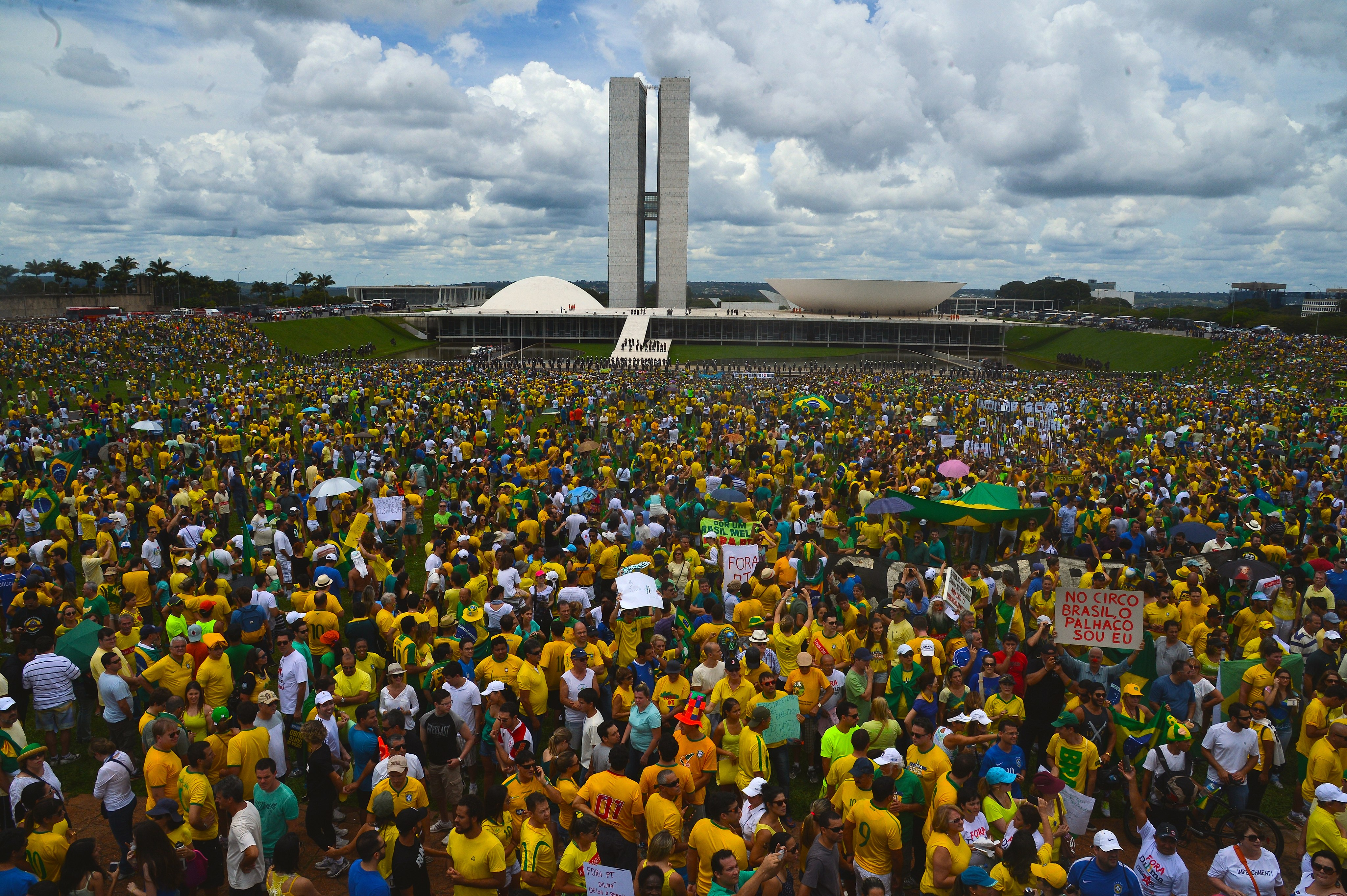 A large crowd of anti-corruption protesters dressed predominantly in the yellow and green of the Brazilian flag stands in front of the Congresso Nacional, designed by Oscar Niemeyer, in Brasilia, Brazil.