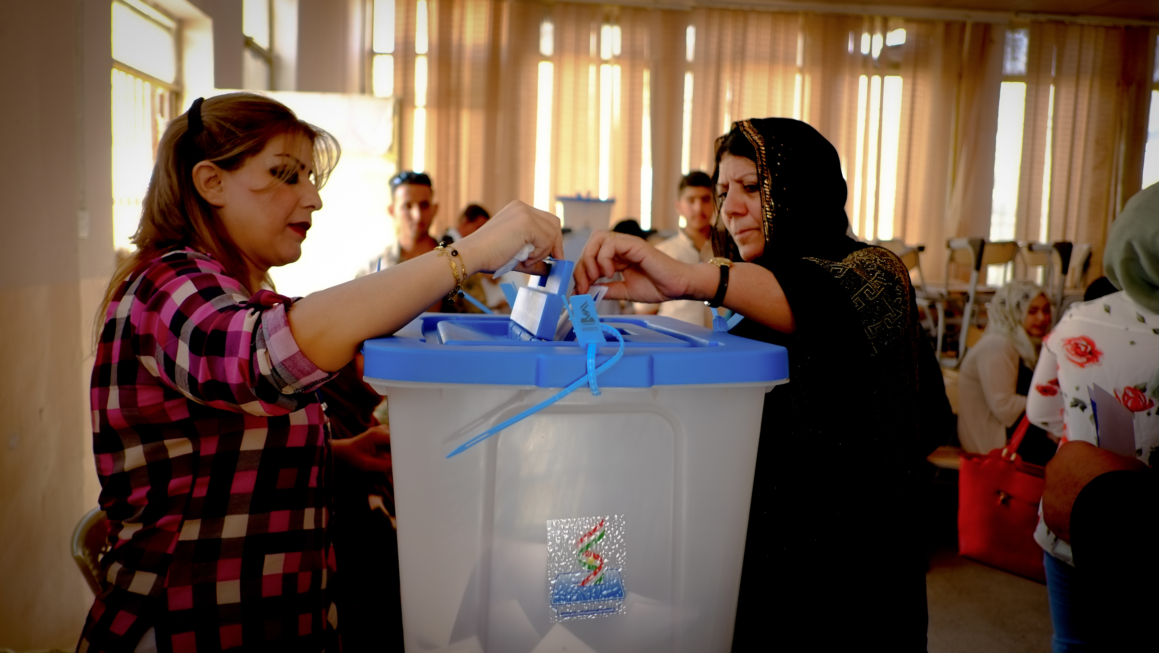 A Kurdish woman puts casts her ballot. Another Kurdish woman holds the cover of the voting slot open.