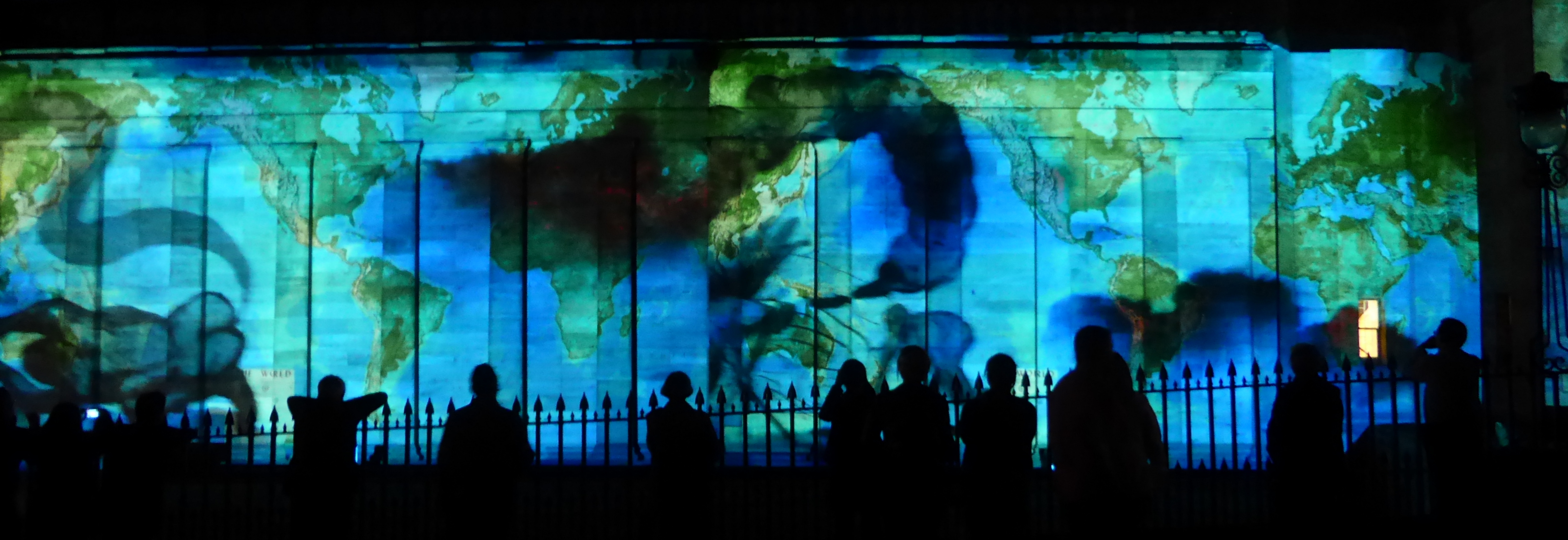 """""""In Search of Vanished Blood"""". Projection at the Edinburgh Fringe Festival. A world map overlaid with black swirls is projected onto a stone building, with people's silhouettes outlined against the light."""