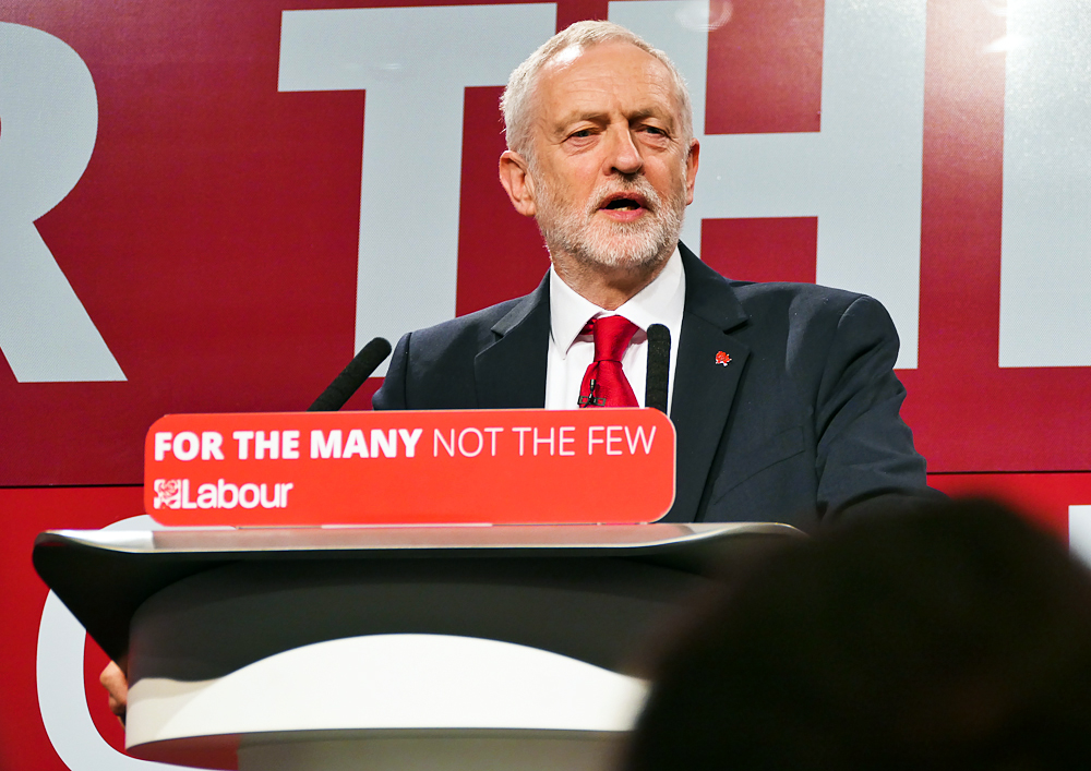 Labour leader Jeremy Corbyn stands on a stage, speaking to his audience ahead of the 2017 UK General Election. He wears a dark suit, white shirt and red tie. On the plinth he is standing at is the slogan: For The Many, Not The Few'. LABOUR'.