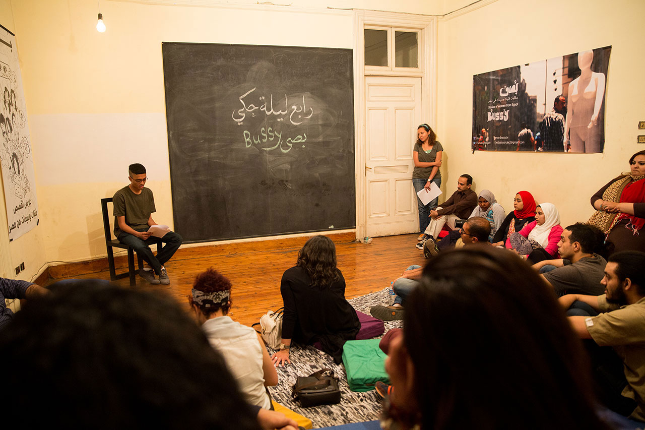 A storytelling night at Bussy in Damascus, which creates safe spaces for Egyptians to recount their experiences. In a bright room with Arabic written on a large blackboard, a young man reads aloud to a group of listeners seated on the floor.
