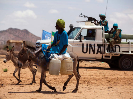 A woman rides a donkey loaded with water jerry cans, while UNAMID troops from Tanzania conduct a routine patrol in the camp for internally displaced persons (IDP) in Khor Abeche, South Darfur. In the foreground a woman rides a heavily laden donkey with a UN armed truck in the background.